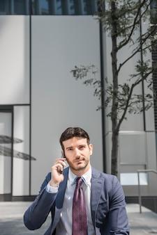 Przystojny biznesmen ma rozmowę telefoniczną