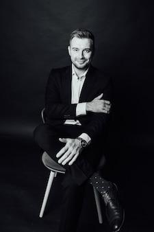 Przystojny biznesmen mężczyzna siedzi na krześle w studio fotograficznym