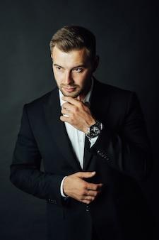 Przystojny biznesmen mężczyzna w garniturze pozowanie w studio fotograficznym.