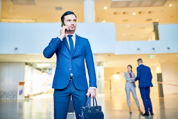 Przystojny biznesmen mówiąc przez telefon na lotnisku
