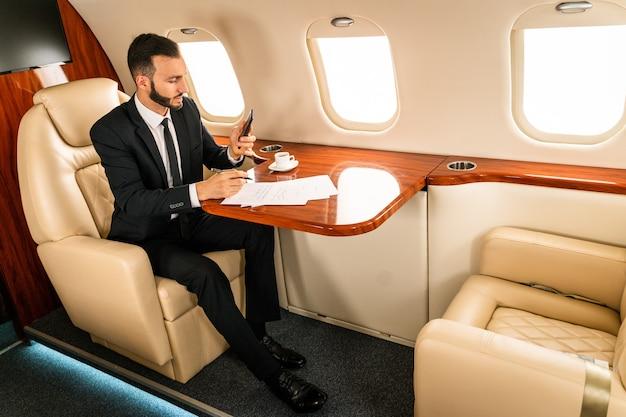 Przystojny biznesmen na sobie elegancki garnitur latający na ekskluzywny prywatny odrzutowiec