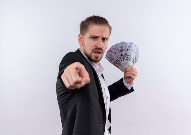 Przystojny biznesmen na sobie garnitur pokazując gotówkę, wskazując palcem wskazującym na aparat z gniewną twarzą stojącą na białym tle