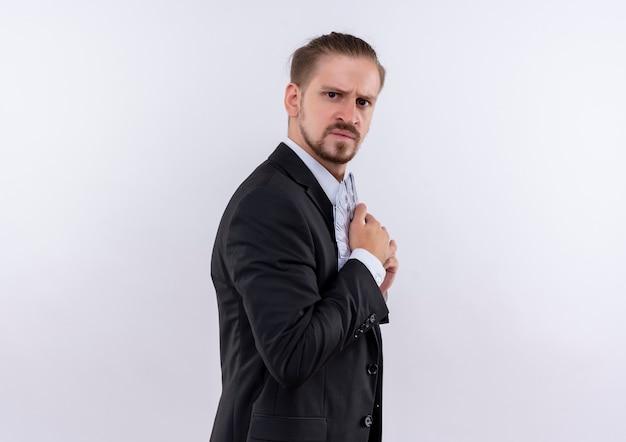 Przystojny biznesmen na sobie garnitur, ukrywając pieniądze w jego garniturze z poważną twarzą stojącą na białym tle