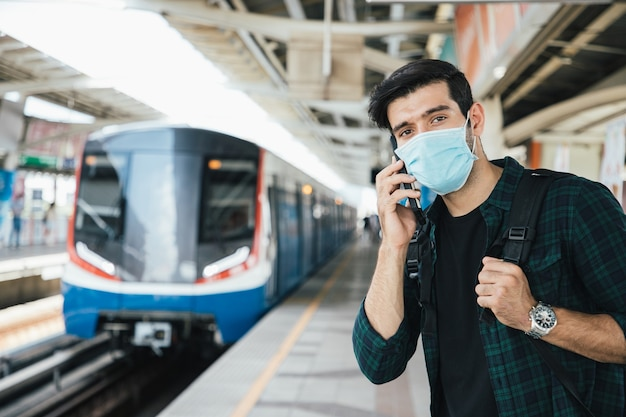 Przystojny biznesmen noszący chirurgiczną maskę na twarz przeciwko nowemu koronawirusowi lub chorobie koronawirusowej covid i używający smartfona na stacji kolejowej public sky zrelaksuj się i słuchaj muzyki w drodze
