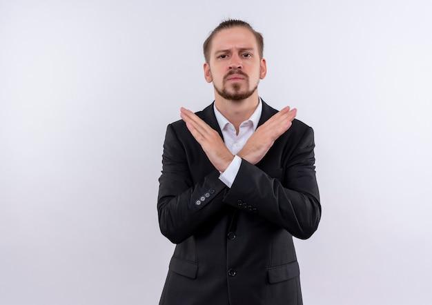 Przystojny biznesmen noszenie garnituru co znak stopu przekraczania ramion patrząc na kamery z poważną twarzą stojącą na białym tle