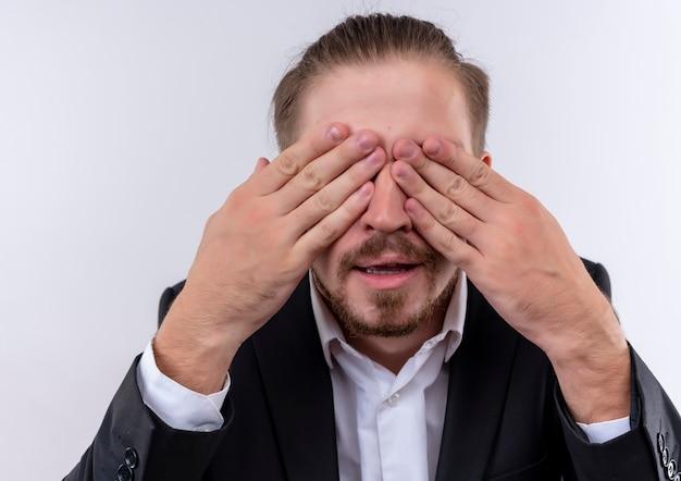 Przystojny biznesmen noszenie garnituru obejmującego oczy z rękami stojącymi na białym tle