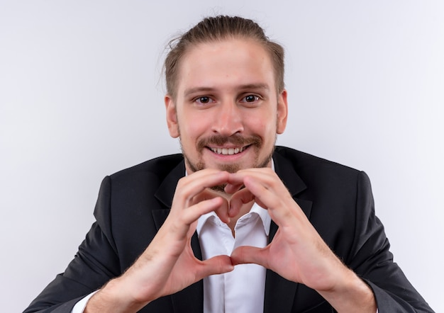 Przystojny biznesmen noszenie garnituru okiem gest serca palcami patrząc na cmera z uśmiechem na twarzy stojącej na białym tle