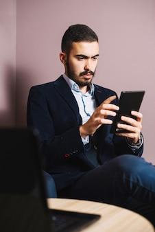 Przystojny biznesmen oglądania tabletu
