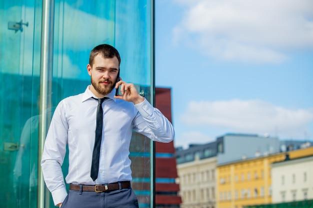 Przystojny biznesmen opowiada telefonem komórkowym