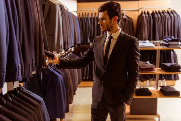 Przystojny biznesmen patrzeje klasycznego kostium i wybiera.