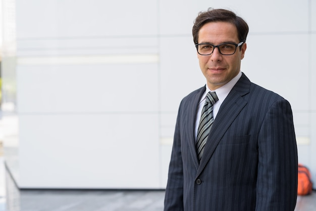 Przystojny biznesmen perski pozuje przed białą ścianą