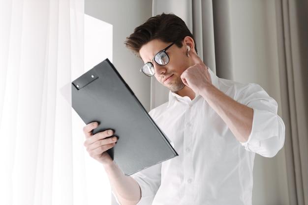 Przystojny biznesmen pewnie stojąc przy oknie w pomieszczeniu, trzymając tablet, na sobie bezprzewodowe słuchawki