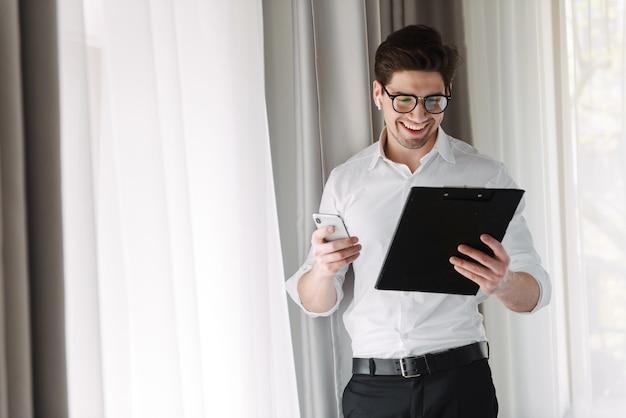 Przystojny biznesmen pewnie stojąc przy oknie w pomieszczeniu, trzymając tablet, nosząc słuchawki bezprzewodowe, trzymając telefon komórkowy