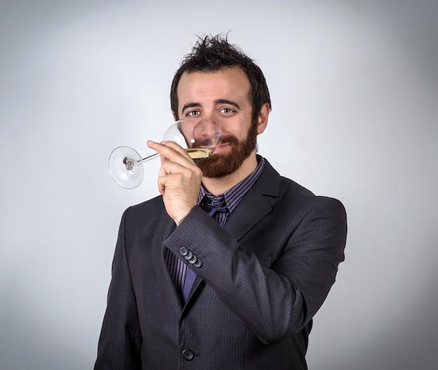 Przystojny biznesmen pije białe wino