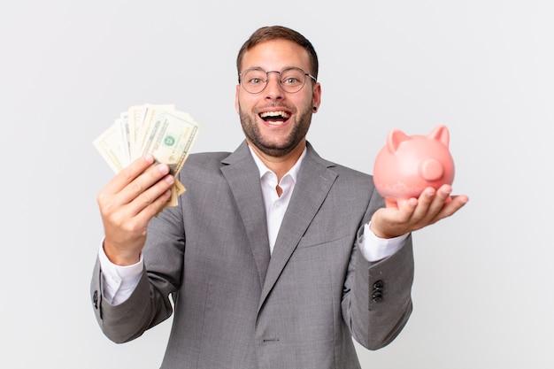 Przystojny biznesmen posiadający skarbonka. koncepcja oszczędności