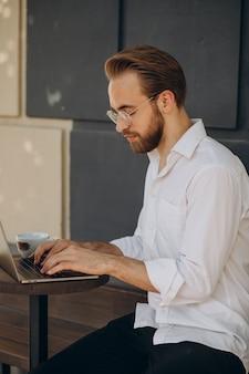 Przystojny biznesmen pracujący online na komputerze z kawiarni