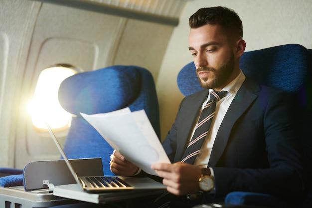 Przystojny biznesmen pracuje w samolocie
