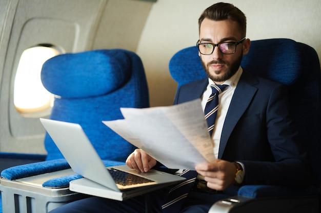 Przystojny biznesmen pracy w samolocie