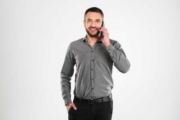 Przystojny biznesmen rozmawia przez telefon komórkowy.