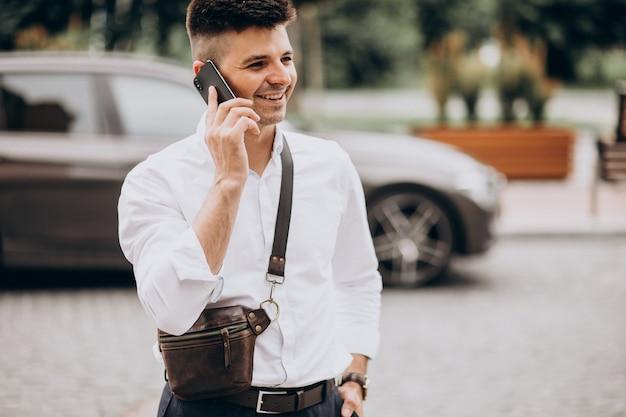 Przystojny biznesmen rozmawia przez telefon swoim samochodem