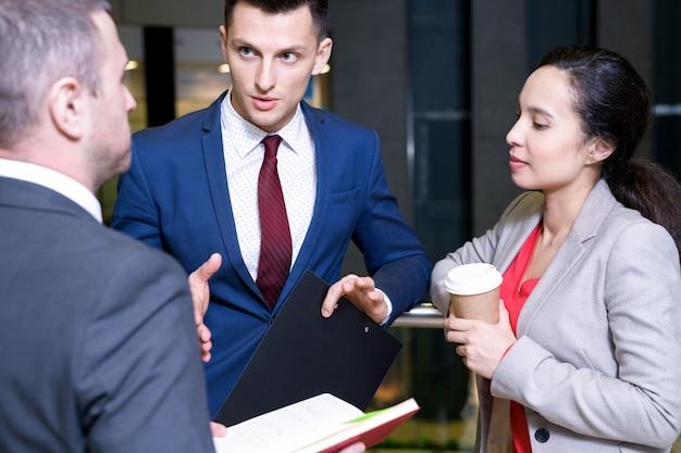 Przystojny biznesmen rozmawia z kolegami