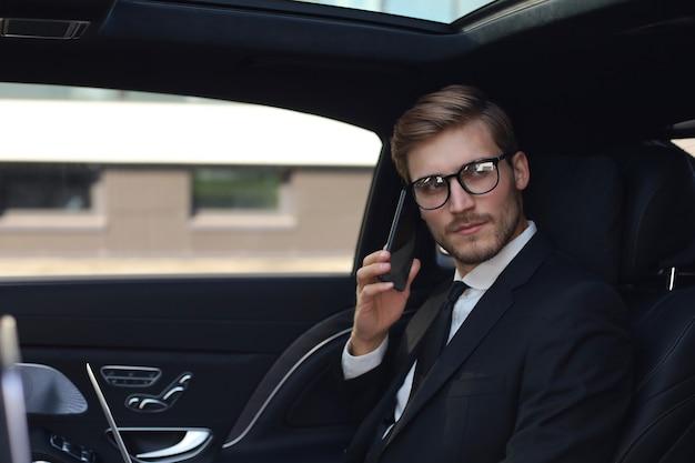 Przystojny biznesmen rozmawia z telefonem siedząc z laptopem na tylnym siedzeniu samochodu.