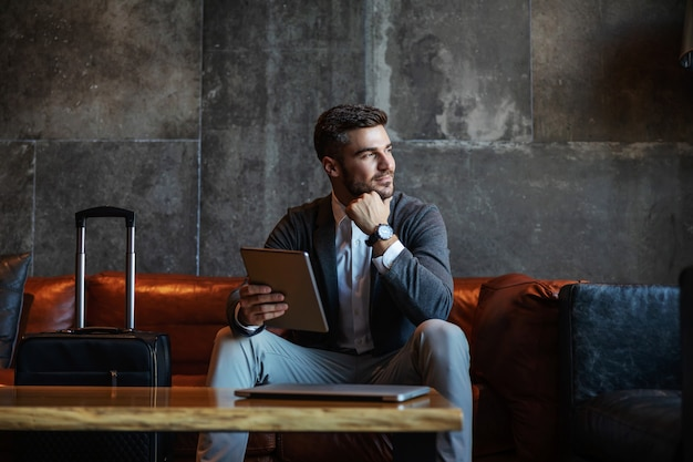 Przystojny biznesmen siedzi na hotelowej kanapie i trzyma tablet