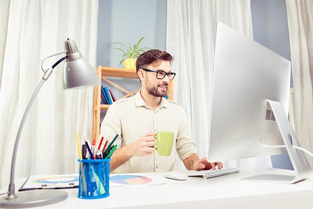 Przystojny biznesmen siedzi przy stole i trzymając filiżankę kawy