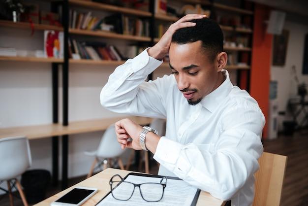 Przystojny biznesmen siedzi przy stole, patrząc na zegarek