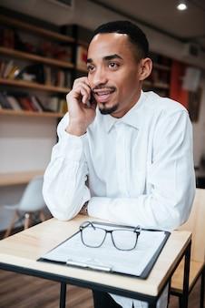 Przystojny biznesmen siedzi przy stole rozmawia przez telefon