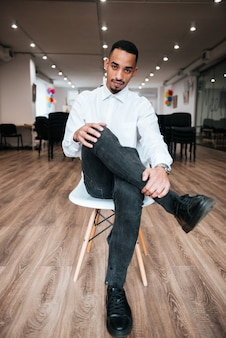 Przystojny biznesmen siedzi w biurze