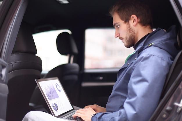 Przystojny biznesmen siedział w luksusowej limuzynie, pracując na komputerze przenośnym