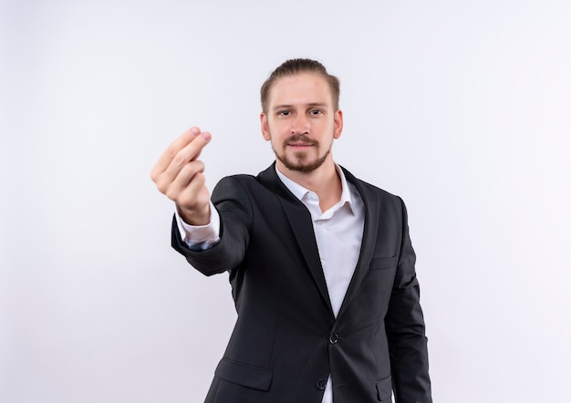 Przystojny biznesmen sobie garnitur patrząc na kamery pocieranie palcami zarabianie pieniędzy gest stojąc na białym tle