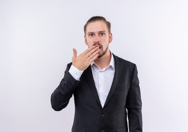 Przystojny biznesmen sobie garnitur patrząc zaskoczony i zdumiony, obejmujące usta ręką stojącą na białym tle