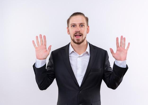 Przystojny biznesmen sobie garnitur pokazując numer dziesięć uśmiechnięty wesoło stojąc na białym tle