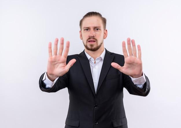 Przystojny biznesmen sobie garnitur robi znak stopu z otwartymi rękami patrząc na kamery z poważną twarzą stojącą na białym tle