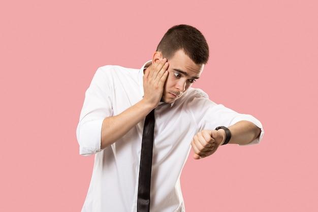 Przystojny biznesmen sprawdzanie jego zegarka na różowym tle. łał. atrakcyjny męski portret z przodu do połowy długości