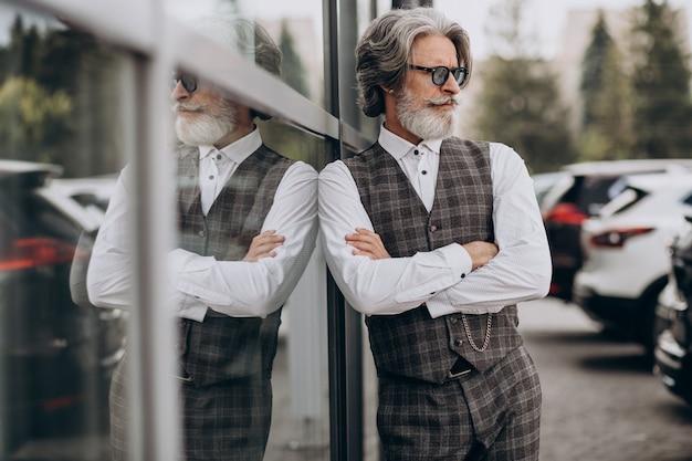 Przystojny biznesmen stojący na zewnątrz i myśli