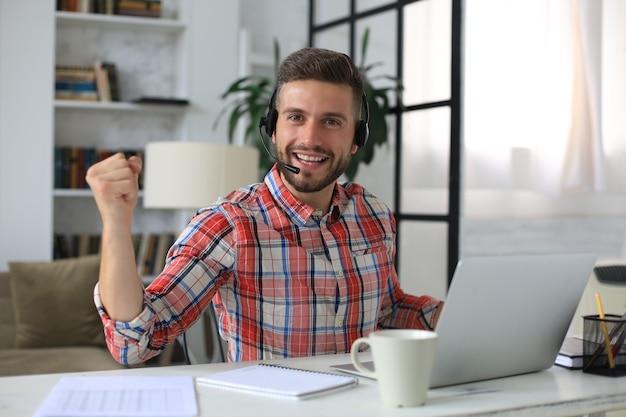 Przystojny biznesmen trzyma podniesione ręce i wyraża radość w domowym biurze.