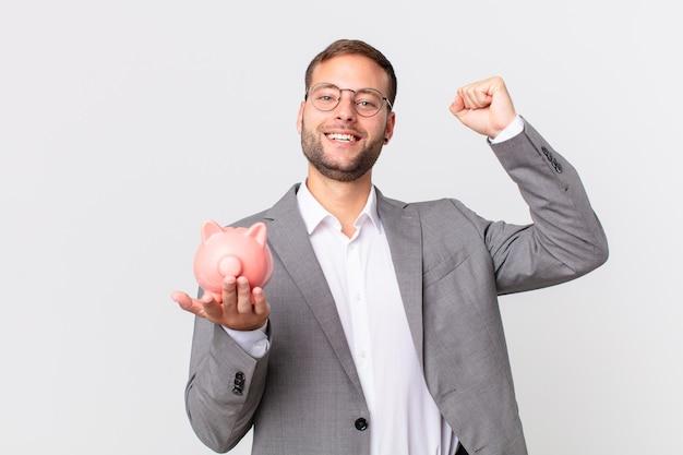 Przystojny biznesmen trzyma skarbonkę. koncepcja oszczędności
