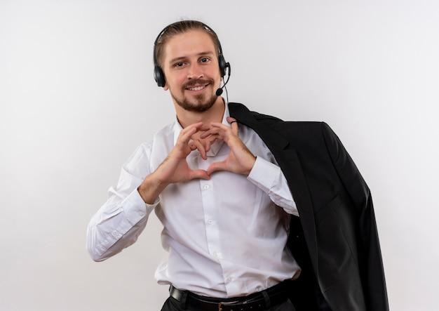 Przystojny biznesmen trzymając kurtkę na ramieniu ze słuchawkami z mikrofonem, czyniąc gest serca palcami uśmiechnięty stojący na białym tle