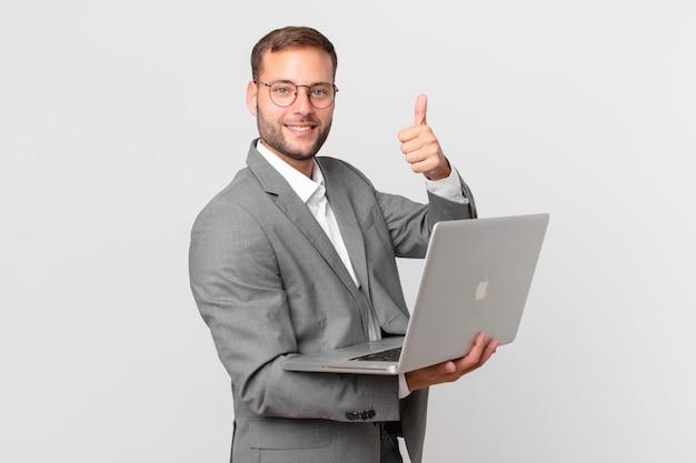 Przystojny biznesmen trzymający laptopa