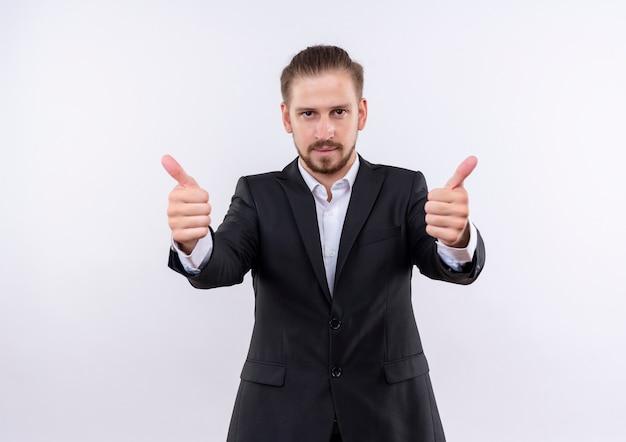 Przystojny biznesmen ubrany w garnitur uśmiechnięty, patrząc na kamery pokazujące kciuki do góry obiema rękami stojąc na białym tle