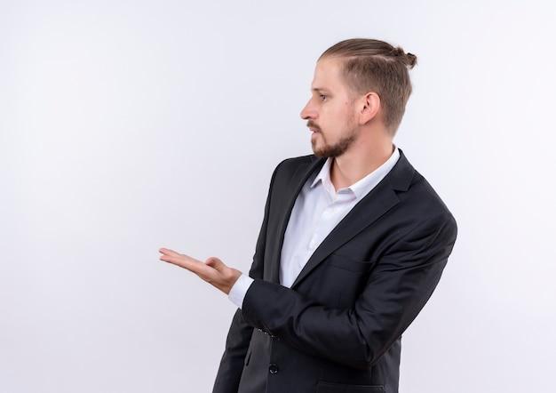 Przystojny biznesmen ubrany w garnitur, wskazując ręką na boku stojącego na białym tle