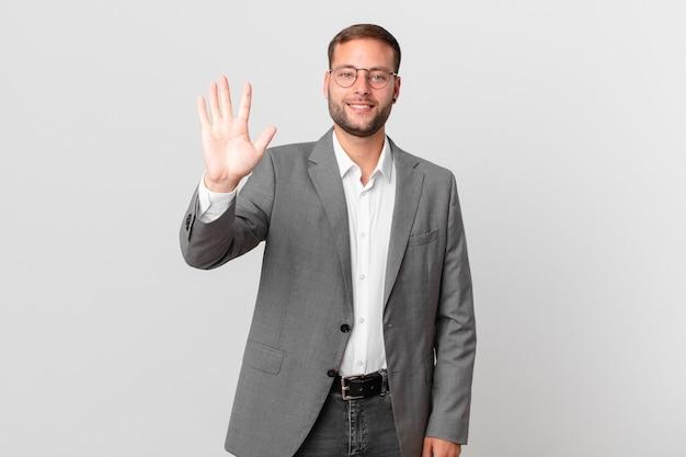 Przystojny biznesmen uśmiecha się i wygląda przyjaźnie, pokazując numer pięć