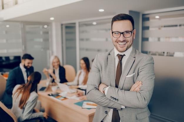 Przystojny biznesmen uśmiechający się w wizytowym i okulary stojąc w sali konferencyjnej z rękami skrzyżowanymi. miłość i szacunek nie towarzyszą automatycznie kierownictwu.