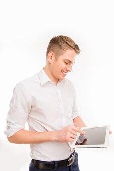 Przystojny biznesmen uśmiechający się za pomocą tabletu w swojej pracy