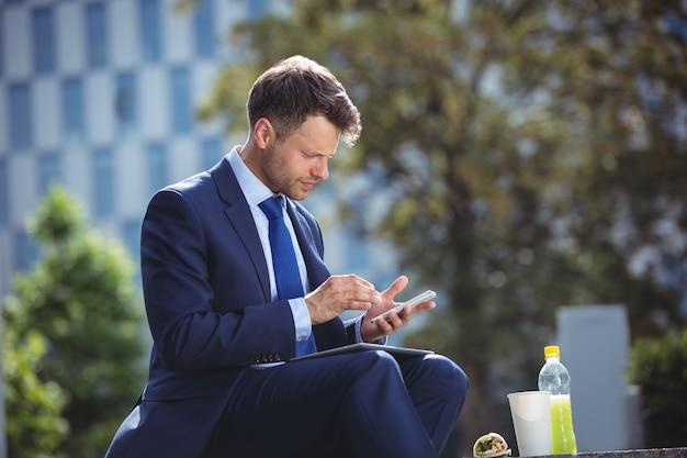Przystojny biznesmen używa telefon komórkowego