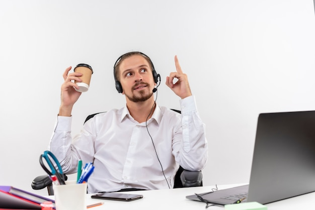 Przystojny biznesmen w białej koszuli i słuchawkach z mikrofonem, trzymając filiżankę kawy, wskazując palcem w górę, uśmiechając się, siedząc przy stole w biurze na białym tle