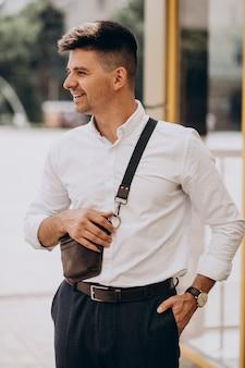Przystojny biznesmen w białej koszuli na zewnątrz